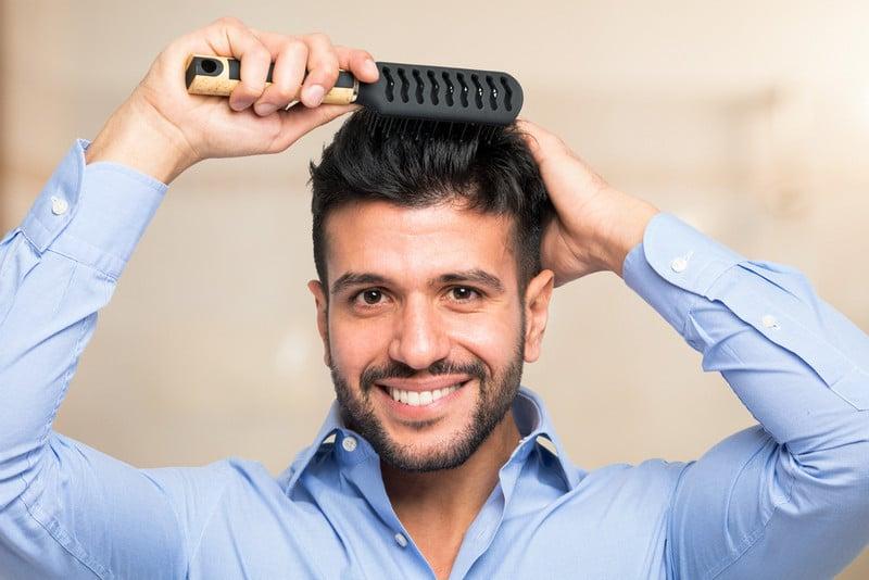 Мужчина демонстрирует свои густые волосы после пересадки